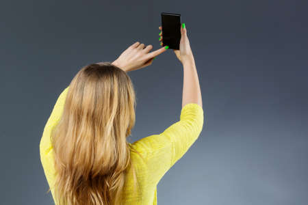Unrecognizable woman taking selfie photo