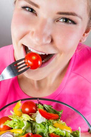 Close up of woman eating salad photo