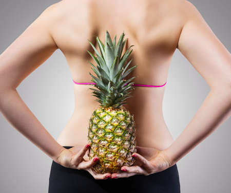 unrecognizable: Unrecognizable fit woman with pineapple