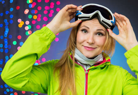 raised eyebrows: Woman in ski clothing on christmas lights Stock Photo