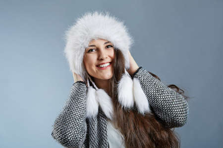 widely: A photo of young woman wearing warm clothes, with fluffy cap on her head. Shes smiling widely. Stock Photo