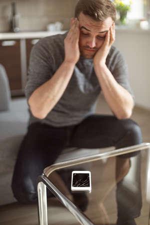 smart man: Worried man looking at broken smart phone