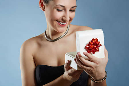 chignon: A photo of young, elegant woman holding an open present box. Shes very happy.