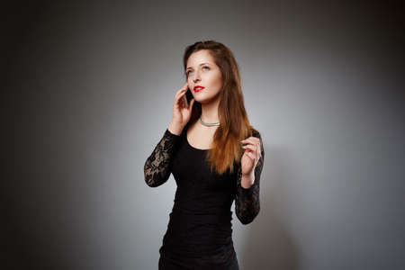 womanlike: A photo of young, beautiful woman talking on the mobile phone. Shes waring all in black.