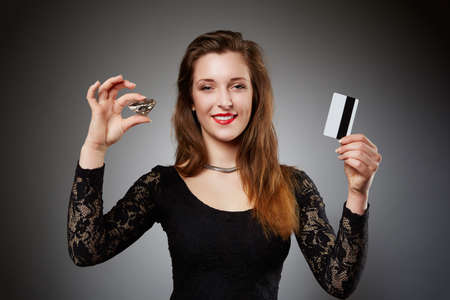 auburn hair: A photo of young, beautiful woman holding a diamond in one hand and debit card in second. Shes wearing all in black. Stock Photo