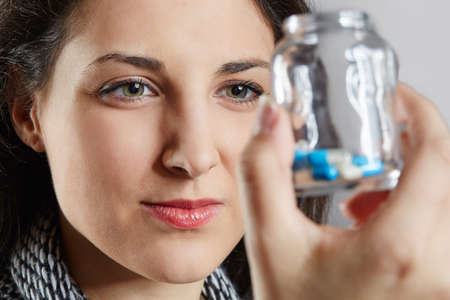 mental disorder: Close up of a woman holding pill container and looking at it Stock Photo
