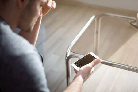 woeful: Woeful man holding damaged smart phone