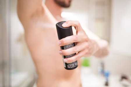 deodorant: Close up of a man applying deodorant, standing in bathroom.