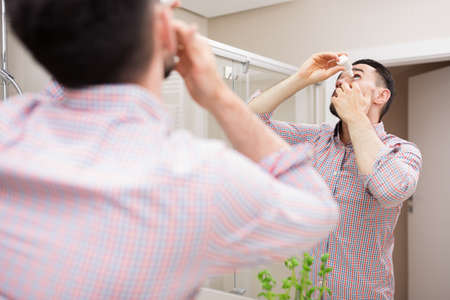 hispanic ethnicity: Man using eyedrops standing in bathroom by the mirror. Casual clothing, hispanic ethnicity.