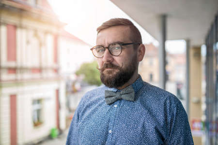 30 34 years: Stylish bearded man in bow tie and blue shirt standing on a terrace