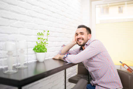 casual clothing: Young man sitting in kitchen and smiling Stock Photo