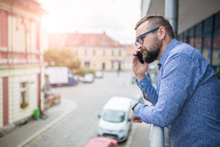 people   lifestyle: Man on the phone standing at balcony Stock Photo