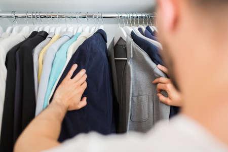 fashion boutique: Unrecognizable man choosing jacket in his wardrobe. Selective focus.