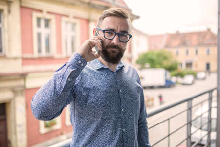 30 34 years: Fashion man standing at terrace and having phone call Stock Photo