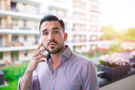 30 34 years: Young elegant man talking on the phone at balcony with a view Stock Photo
