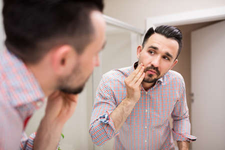 rolled up sleeves: Handsome man examining his face in the mirror. Man is wearing casual shirt with rolled up sleeves. He is standing in domestic bathroom.