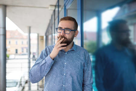 30 34 years: Man in blue shirt standing outside the office and smoking cigarette Stock Photo