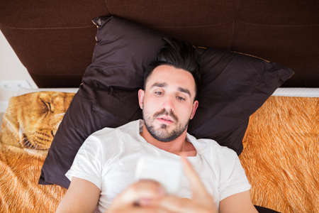 net surfing: Man surfing the net on his smart phone in bed