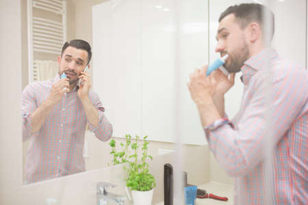 adult brushing teeth: Man standing in bathroom, brushing teeth and having phone call. He is using electric toothbrush, looking away and wearing casual shirt with rolled up sleeves.
