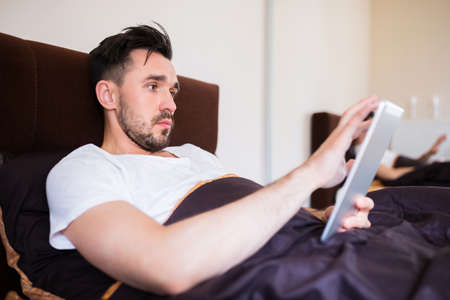 surfing the net: Man surfing the net on tablet in bed Stock Photo