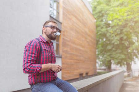 hombre fumando: Hombre que fuma conjuntos aire libre