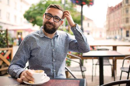 ashamed: hombre sonriente avergonzada sentado en un café y rascarse la cabeza