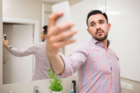 black bathroom: Handsome man taking photo of himself with his smart phone before going out. He looks confident and comfortable. He has beard and black hair.