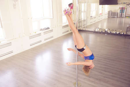 womanlike: A photo of young woman training on dance pole in vertical position. Shes hanging upside down. Stock Photo