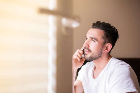 spanish looking: Handsome latino in white t-shirt talking on the phone. Young spanish man with beard sitting in sunshine by open window in bedroom and looking outside. Warm colors.