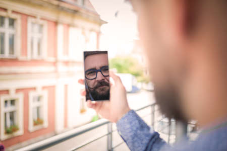 35 years old man: Reflection of a mans face in mobile phone