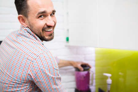 food processor: Joyful young man preparing fresh fruity cocktail in food processor Stock Photo