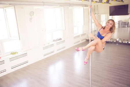 womanlike: A photo of young woman training on dance pole. Shes hanging on the pole and smiling.