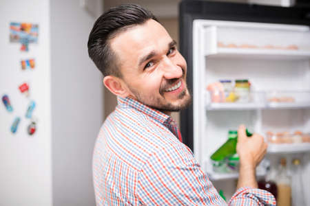 30 34 years: Smiling man holding a beer and standing by the fridge