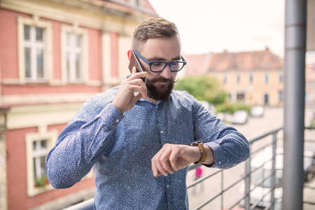 businessman waiting call: Man standing at balcony, looking at hand watch and calling Stock Photo
