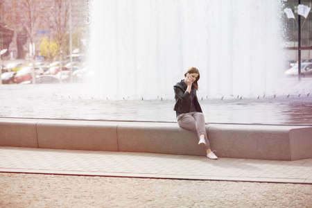 waterworks: Woman sitting by the waterworks and talking on the phone