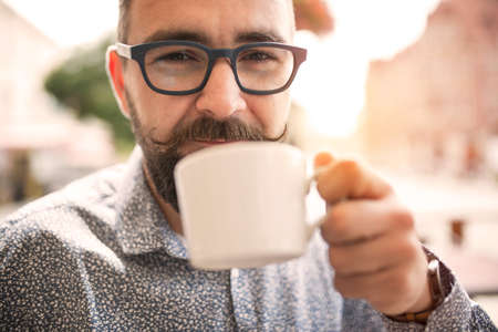holding close: Close up of a man holding mug of coffee in outdoors coffee shop
