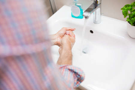 antibacterial: Man washing hands with an antibacterial liquid soap. No face is recognizable.