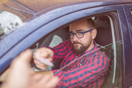 under the influence: Man sitting in car and giving his driving licence through the window