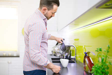 30 34 years: Man standing in kitchen and preparing coffee on kitchen counter. He is holding electric cordless kettle and pouring water into the mug.