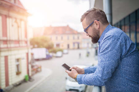 surfing the net: Man standing at balcony and surfing the net on smart phone