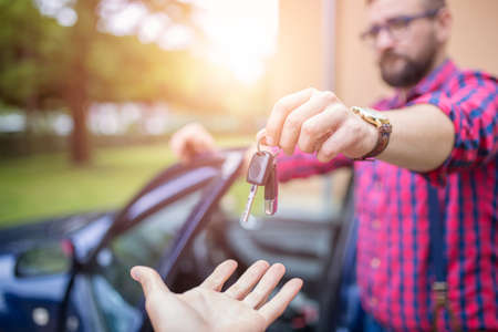annuities: Man standing by the car and giving back car keys