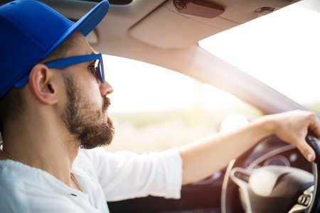 hombres jovenes: Primer plano de un joven que conduce el coche por el sol