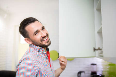 30 34 years: Smiling man standing in kitchen by the closet. White modern kitchen with glossy furniture and white bricks on the wall.