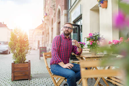 30 34 years: Man sitting in cafe garden and drinking takeaway coffee