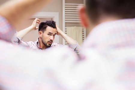 his shirt sleeves: Handsome man in checkered shirt with sleeves rolled up doing his hair style in light bathroom. He is looking at himself in mirror. Stock Photo