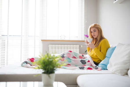 plainness: Lying under the blanket and drinking tea Stock Photo