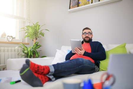 bespectacled man: Happy man lying on the couch