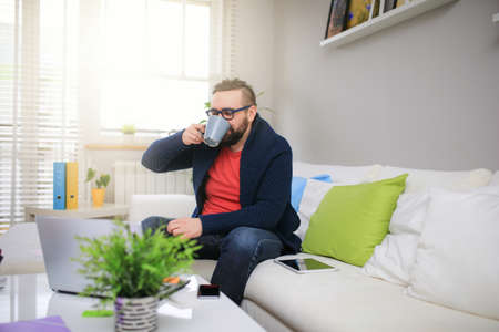 bespectacled man: Coffee break during home work