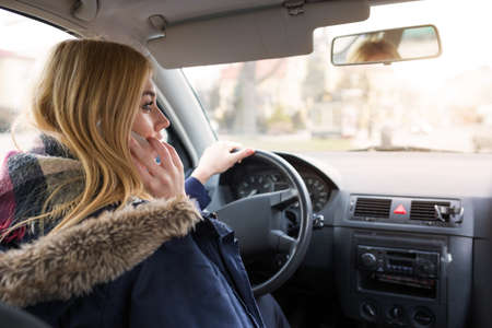 anorak: Girl driving and talking on the mobile Stock Photo