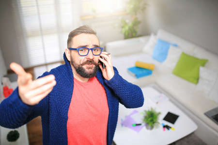 bespectacled man: Man arguing on the phone